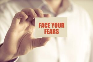 face your fears written on piece of paper held by calgary counselling services client